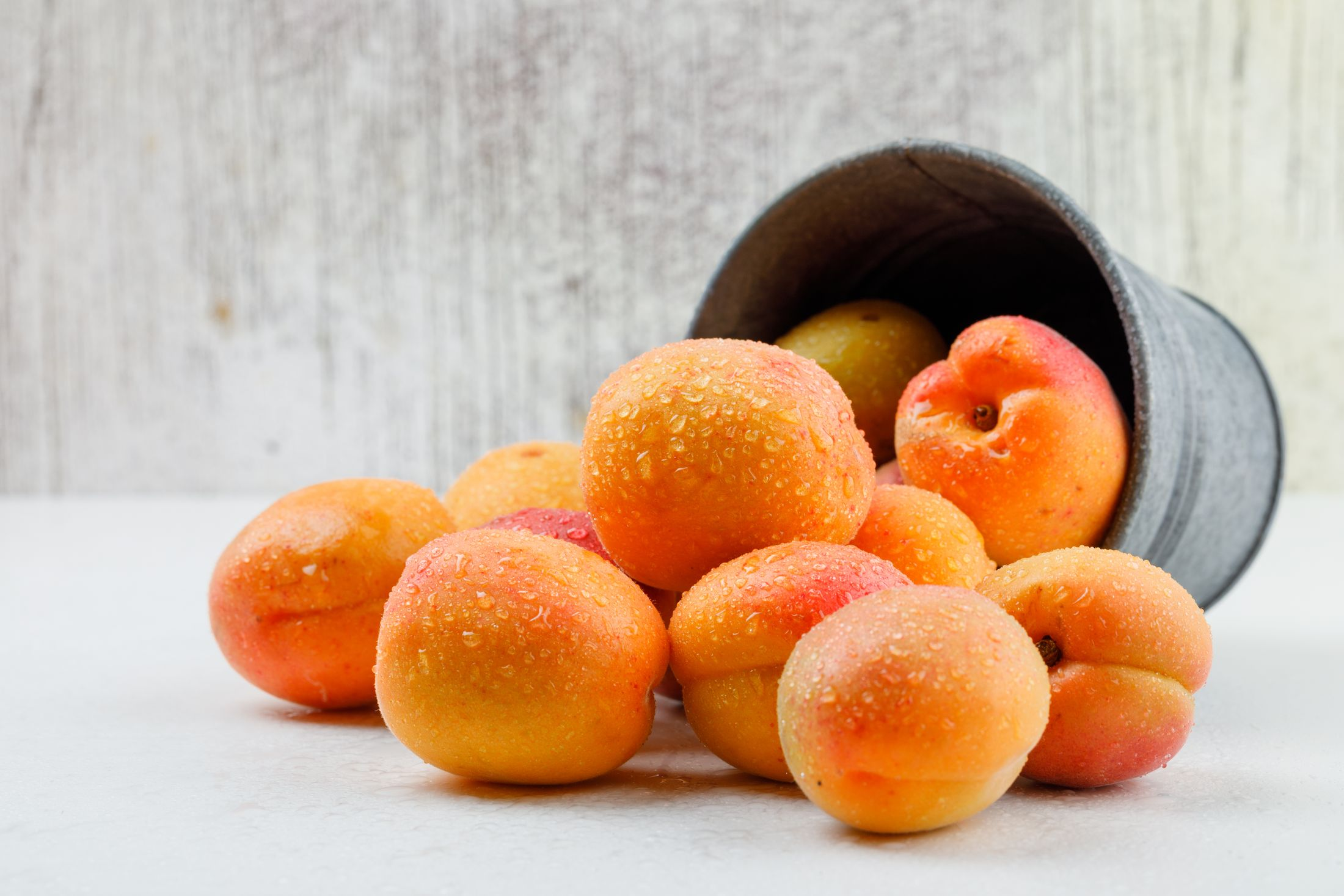 Natural apricots in a mini bucket on white and grunge background. side view.